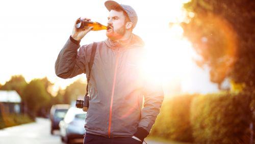 Das Bild zeigt einen jungen Mann, der auf der Straße steht und ein Bier trinkt.