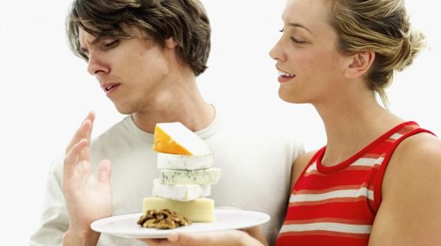 Frau hält Mann einen Teller Käse vor die Nase