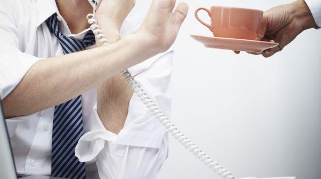 Ein telefonierender Mann lehnt mit einer Handbewegung eine Tasse Kaffee ab.