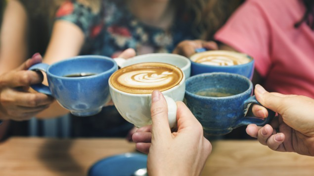 Fünf Freundinnen stoßen mit Kaffee an.