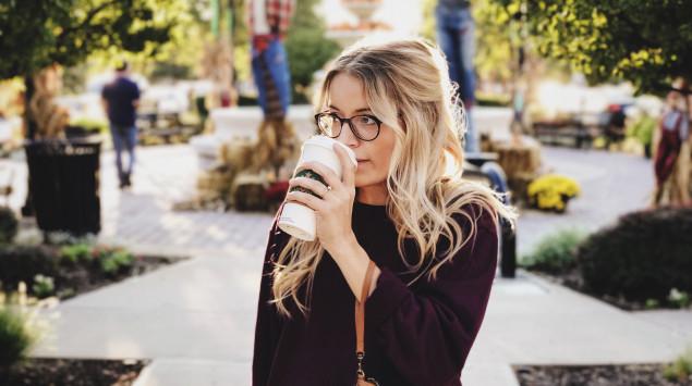 Frau trinkt Kaffee aus einem Starbucks Becher.