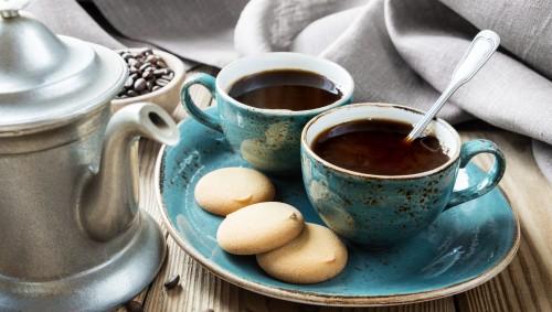 Neben einer silbernen Kaffeekanne steht ein Teller mit zwei Tassen Kaffee und ein paar Plätzchen.