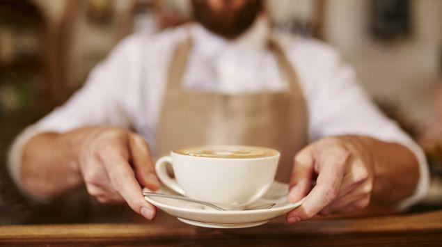 Das Bild zeigt einen Barista mit einer Tasse Kaffee.
