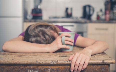 Das Bild zeigt eine junge Frau mit einem Kaffee, die ihren Kopf auf den Tisch gelegt hat.
