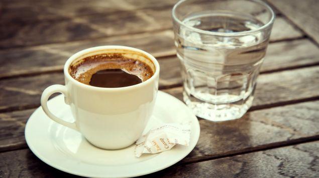 Das Bild zeigt eine Tasse Kaffee neben einem Glas Wasser.