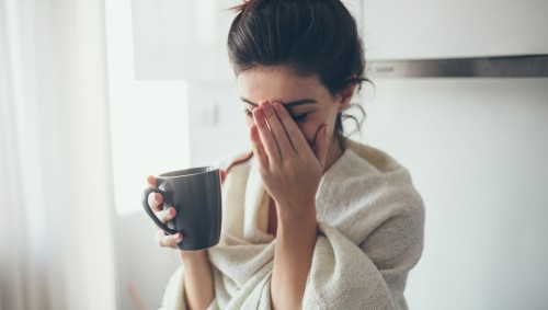 Eine junge, in ein Tuch gehüllte Frau hält eine Kaffeetasse in der rechten Hand und greift sich mit der linken Hand ins Gesicht.