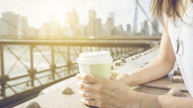 Eine Frau lehnt an einem Brückengeländer und hält einen Kaffeebecher in den Händen.