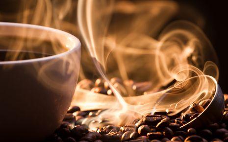 Das Bild zeigt ein paar Kaffeebohnen neben einer Tasse.