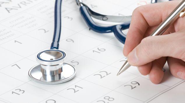 Jemand notiert etwas in seinem Kalender, daneben liegt ein Stethoskop.