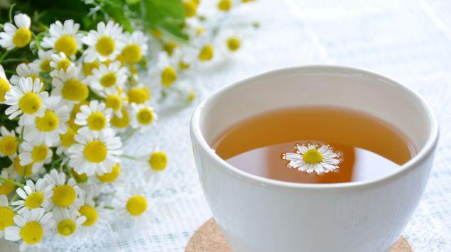 Eine Tasse Kamillentee, daneben frische Kamillenblüten.