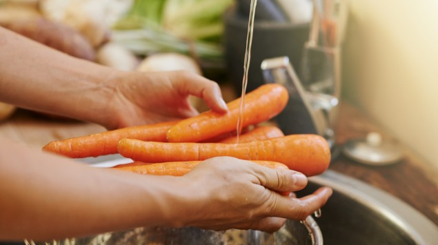 Jemand wäscht Karotten.