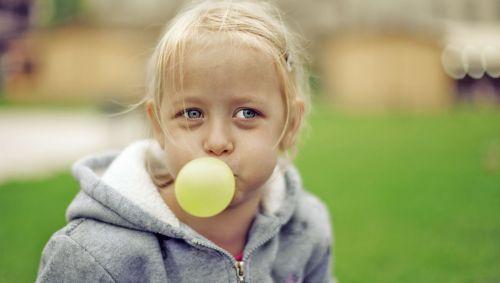 Das Bild zeigt ein kleines Mädchen, das mit einem Kaugummi eine Blase macht.