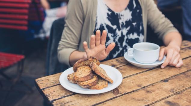Eine Frau lehnt einen Teller mit Brot ab.