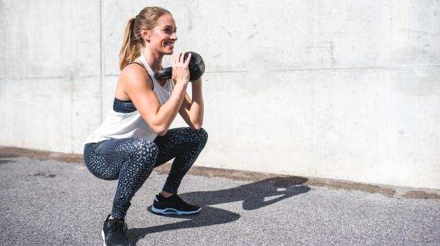 Eine Frau trainiert draußen mit einer Kettlebell.