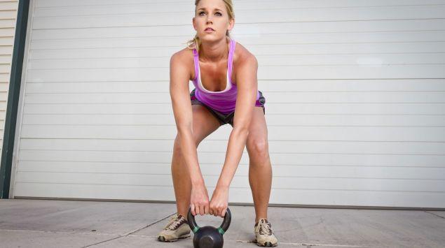 Das Bild zeigt eine Frau, die eine Kettlebell anhebt.