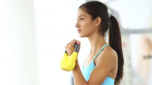 Das Bild  zeigt eine Frau, die eine gelbe Kettlebell in der Hand hält.