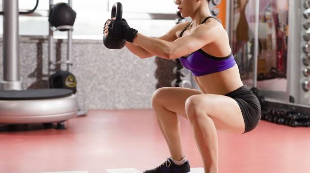 Das Bild zeigt eine Frau, die mit einer Kettlebell eine Kniebeuge macht.