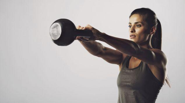 Das Bild zeigt eine Frau, die eine Kettlebell schwingt.