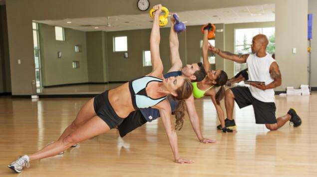 Das Bild zeigt Sportler, die im Seitstütz mit Kettlebells trainieren.