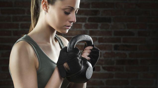 Das Bild zeigt eine Frau, die eine Kettlebell in den Händen hält.