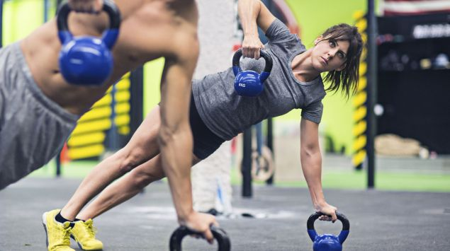 Das Bild zeigt zwei Sportler im Seitstütz auf einer Kettlebell.