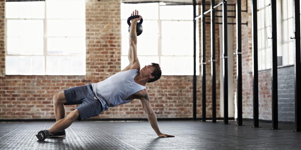Das Bild zeigt einen Mann, der mit einer Kettlebell trainiert.