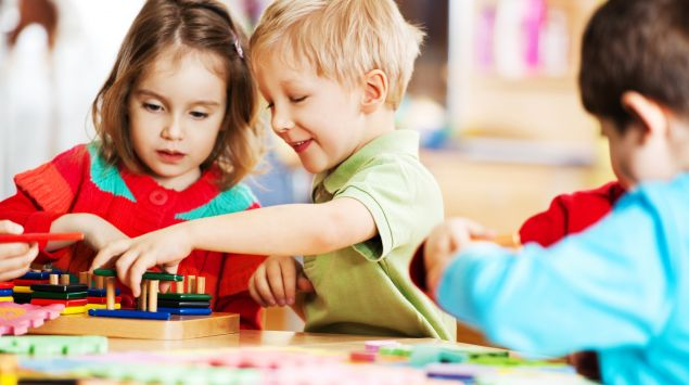 Drei Kinder spielen im Kindergarten an einem Tisch.