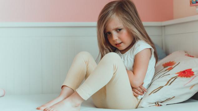 Ein Mädchen sitzt auf einem Bett und hält sich den Bauch