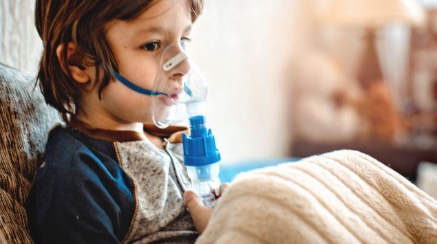 Man sieht einen Jungen mit einem Inhalationsgerät.