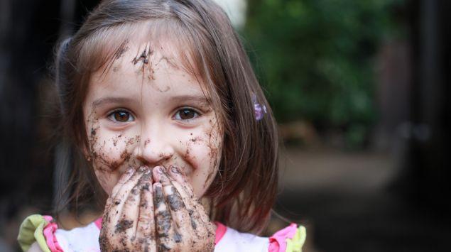 Ein kleines Mädchen hält sich seine schlammverschmierten Hände vor den Mund.