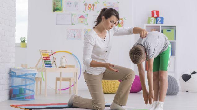 Eine Frau prüft den Wirbelsäulenverlauf eines Jungen.