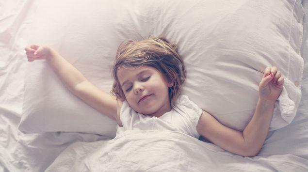 Ein Kind liegt im Bett und streckt sich.