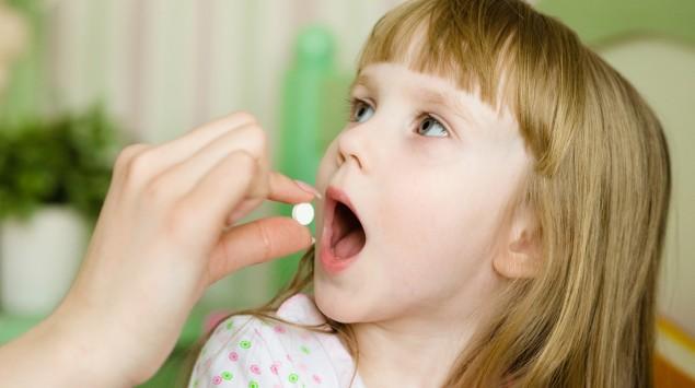 Ein Mädchen bekommt eine Tablette verabreicht.