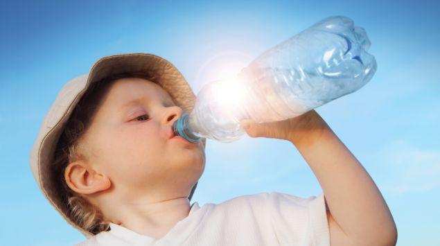 Ein Kind trinkt aus einer Flasche.
