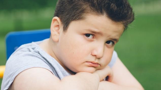 Ein übergewichtiger Junge schaut traurig in die Kamera.