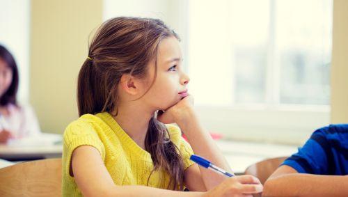 Ein Mädchen träumt in der Schulklasse.
