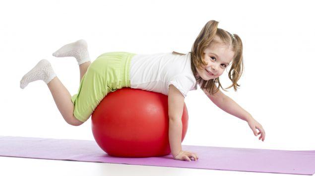 Mädchen balanciert auf dem Bauch auf einem Gymnastikball.