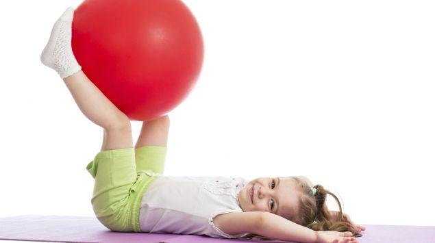 Kind balanciert auf dem Rücken liegend einen Gymnastikball zwischen den Beinen.