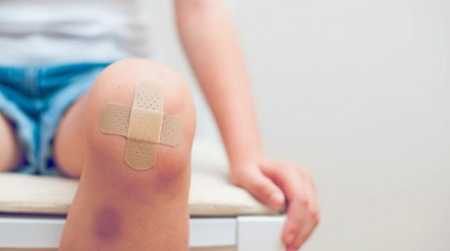 Man sieht ein Kind mit einem blauen Fleck am Schienbein und einem Pflaster auf dem Knie.