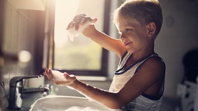 Junge wäscht Hände im Seifenbad im Waschbecken
