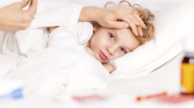 Ein Kind liegt krank im Bett und die Mutter misst Fieber.