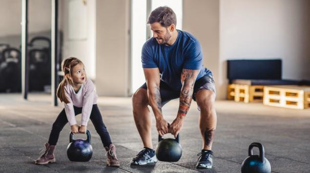 Ein Mann und ein Mädchen in einem Trainingsraum heben Kettlebells an.