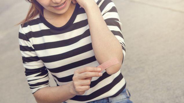 Ein Mädchen klebt sich ein Pflaster auf den Ellenbogen.
