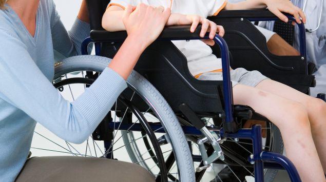 Das Bild zeigt ein Kind in einem Rollstuhl.