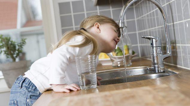 Das Bild zeigt ein Kind, das Wasser aus einem Wasserhahn trinkt.