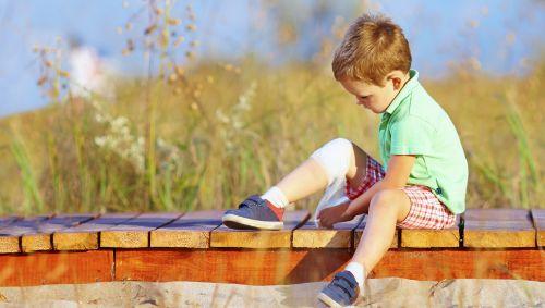 Ein kleiner Junge verbindet sich das Knie.