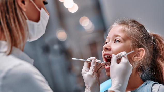 Man sieht ein Kind beim Zahnarzt.