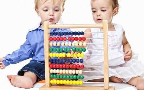 Zwei Kinder spielen mit einem Abakus.