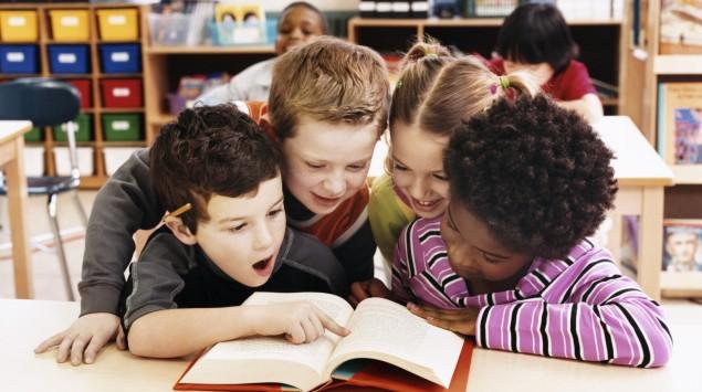 Das Bild zeigt vier Kinder, die gemeinsam an einem Tisch in einem Buch lesen.