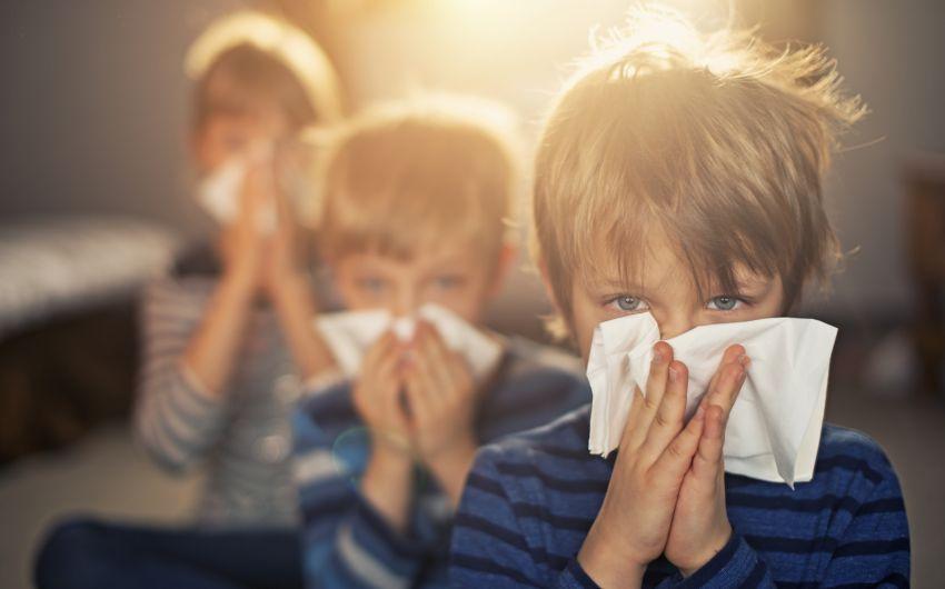 Das Bild zeigt drei Kinder mit Schnupfen, die ihre Nasen putzen.
